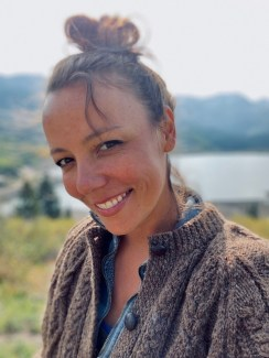 A photograph of the artist outside, smiling in a dark cardigan with her hair tied up in a bun.