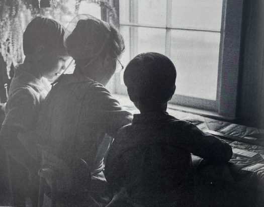 A black-and-white photo of an Amish woman and her two children work on a quilt by the light from a window.