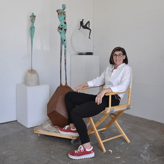 A posed photo of the artist in her studio, with her bronze and resin sculptures behind her.
