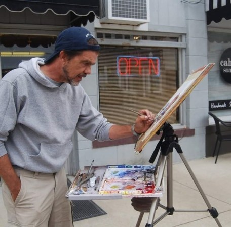 A photograph of the artist in front of a store shop working on a watercolor. He wears a gray sweatshirt, khaki pants, and a blue baseball cap backwards.