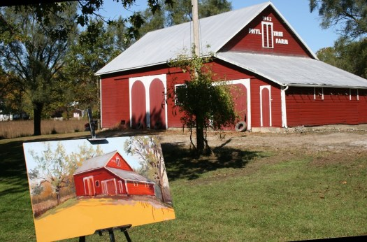 The beginning of a painting of a red barn shows the warm orange-red that underlies the completed composition.