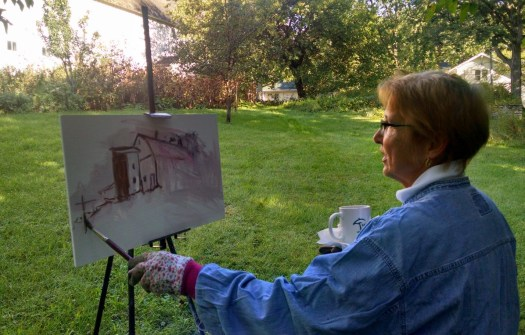 Gwen sits outside, an easel in front of her, with the beginnings of a barn painted onto the otherwise blank composition.