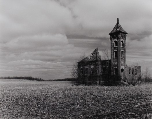 A black-and-white photo of a derelict schoolhouse sitting in a field of plowed crops against a sky of clouds. The roof has completely collapsed, but the bell tower stands strong.