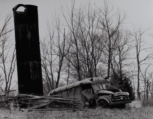 A black-and-white photograph of a school bus left to decompose in a field with sparse trees in the background.