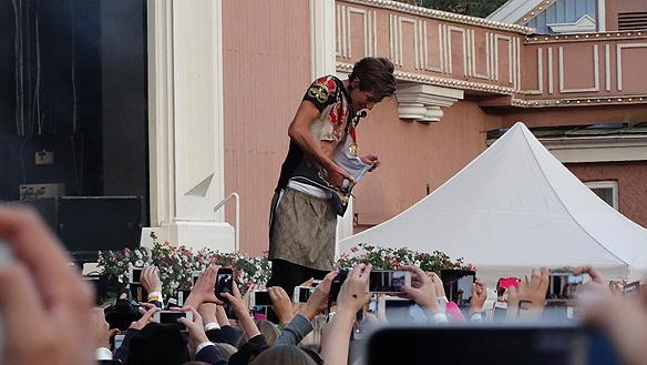 En av medlemmarna i The Fooo tar hjälp av en sax när han inte lyckas att slita av sin T-shirt under konserten på Liseberg. Foto: Peter Ahlborg