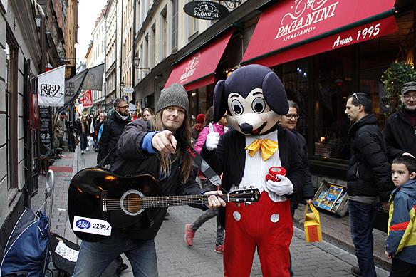 """Tiggarna har blivit kreativa. När Peter Ahlborg spelar i Gamla stan i Stockholm så blir han fotograferad tillsammans med Musse Pigg. Sedan kräver Musse Pigg betalt av min vän Hasse Sukis som tog bilden, """"räcker fram en mugg som är full med ihoprullade sedlar"""". Foto: Hasse Sukis"""