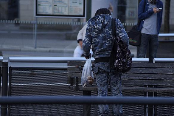 En kille som ska med bussen hittar påsen och tar upp den från marken och lägger den på parkbänken.Foto: Peter Ahlborg