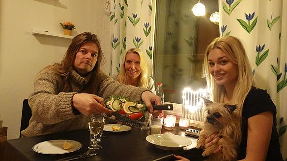 Carina Ekman, Peter Ahlborg, Josefine Ahlborg och lilla vovven Fia, firar med smörgåstårta att Peter Ahlborg har fått en egen lägenhet i november 2014.
