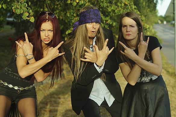 """Peter Ahlborg tillsammans med två hårdrocksbrudar som visar """"djävelns horn"""" med fingrarna. Foto: Hasse Sukis"""