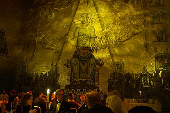 Middag i fantastiska Gyllene Salen. På väggarna finns 18.6 miljoner mosaikbitar i färgat glas med 11 kilo 23,5 karats guld. Guldets värde var 2009 2.8 miljoner. Den praktfulla Mälardrottningen, symbolen för Stockholm, upptar hela norra fondväggen och utgör rummets centralmotiv. Foto: Peter Ahlborg.