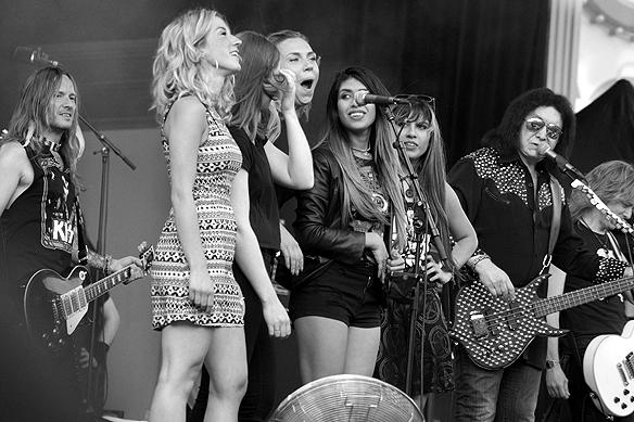 Gene Simmons är en god läromästare och uppmanar här tjejerna som fått komma upp på scenen att komma närmare micken. Foto: Peter Ahlborg