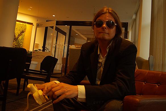 Peter Ahlborg kopplar av med en banan under bevakningen av medlemmarna i Guns N' Roses som mer och mer blir skygga och som gör allt för hålla sig undan, massmedia, fans och vanligt folk. Foto: Charlie Källberg