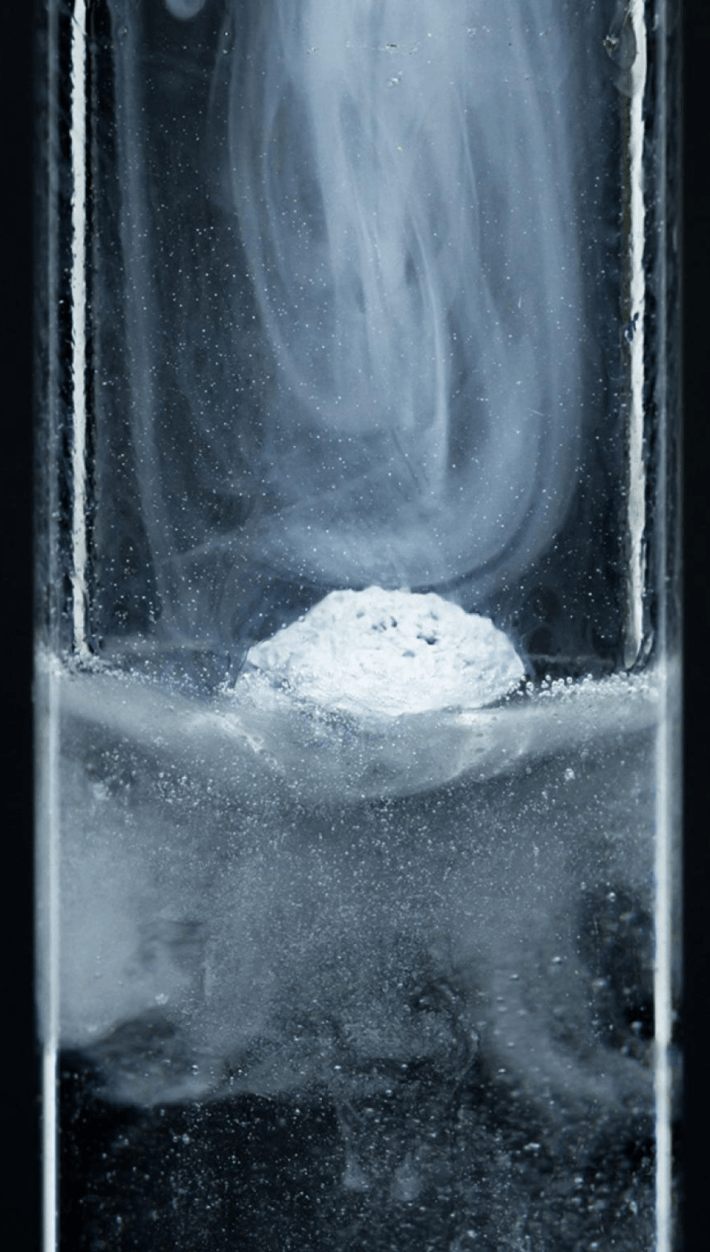 A tube with a white chunky solid floating on a liquid, with a swirling fog-like gas over it