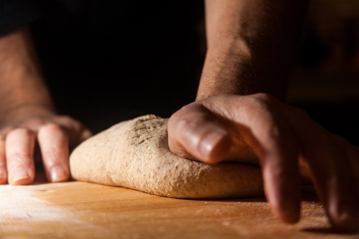 Close-up of two hands kneading bread dough
