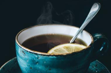 Cup of tea with lemon and spoon.