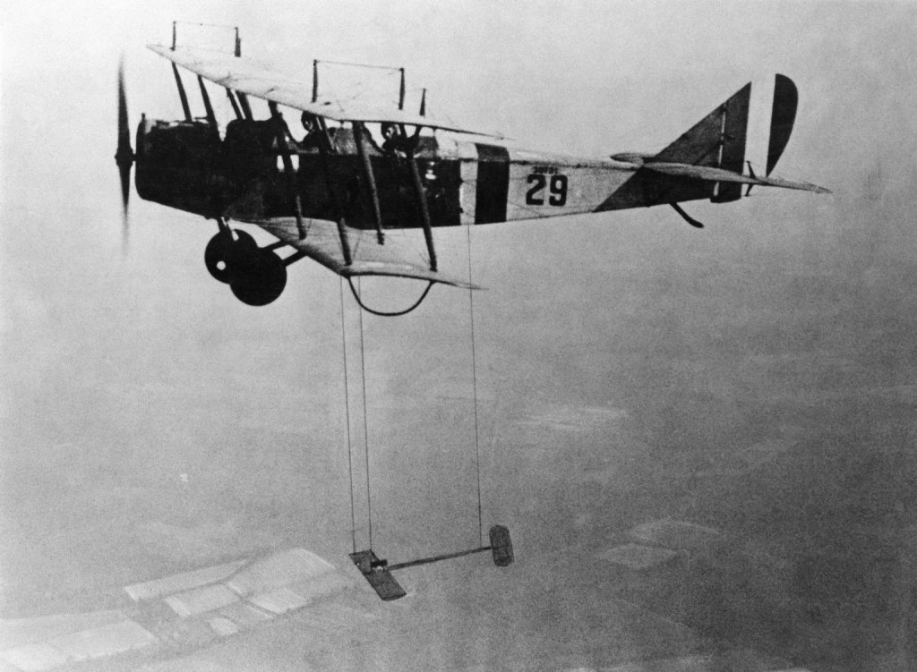 A Curtiss JN-4 biplane (circa 1921) with a model wing suspended below.
