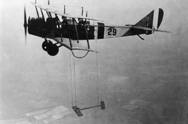 A Curtiss JN-4 biplane with model wing suspended beneath.