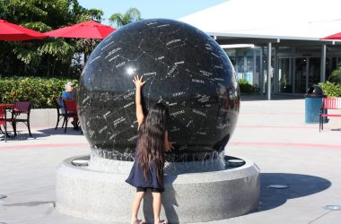 A little girl spins a 9-ton sphere by hand.