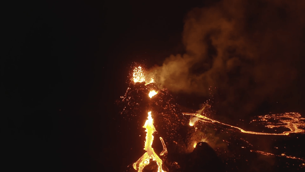 Lava erupts in fountains against the night sky.