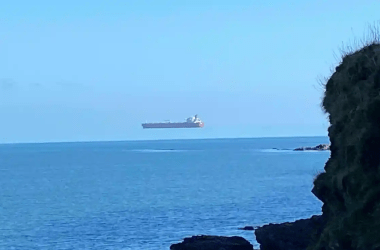 A superior mirage shows a tanker ship appearing to float in the sky.
