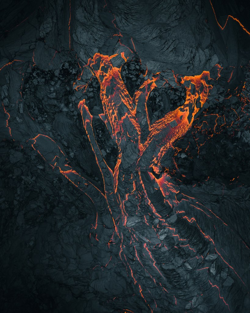 Fingers of lava glow against the black.