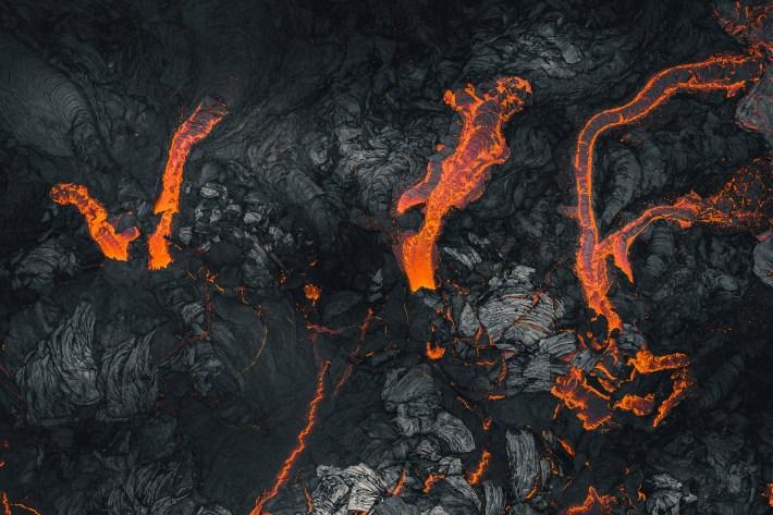 Stripes of orange lava against the black of cooling rock.