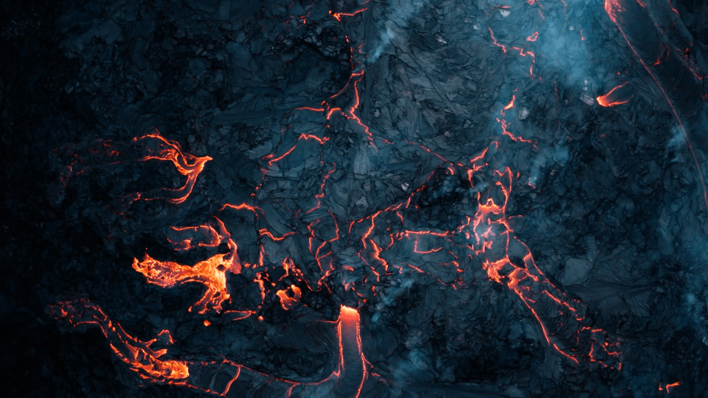 Red lava glows through cracks in the dark, cooling lava.