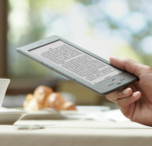 Kindle eReader: Gerät in der Hand im Cafe lesend
