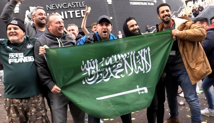 BEST QUALITY AVAILABLE Jubilant Newcastle United fans hold a Saudi flag outside St James' Park whilst celebrating the club's Saudi takeover.
