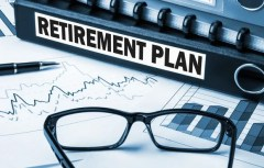 """Binder labeled """"retirement plan"""" next to a pair of glasses and sitting on sheets of graphs"""
