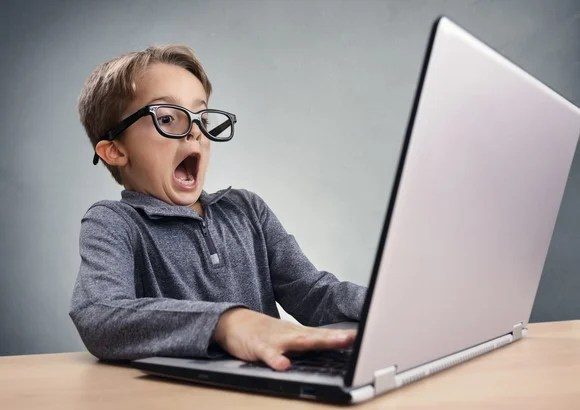 Young boy in glasses at laptop looking astonished, mouth open