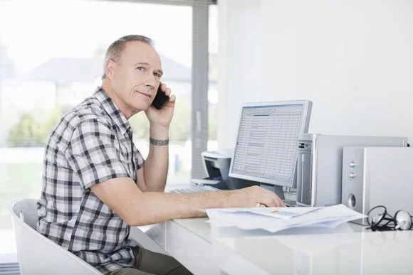 A man sits at a computer desk, talking on the phone.