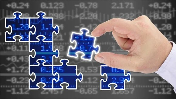 jigsaw pieces being placed over stock prices on a screen