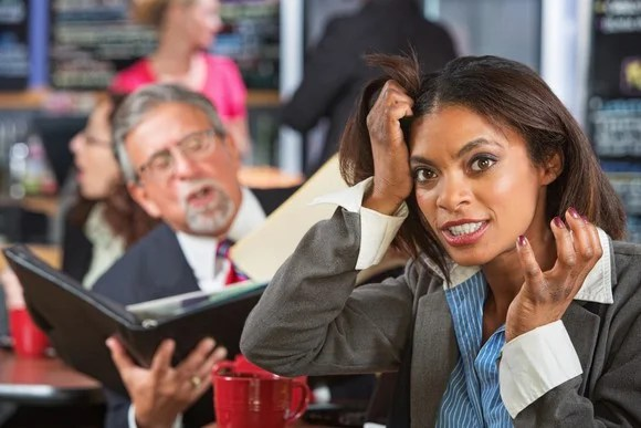 A woman pulls her hair out in annoyance at her co-worker.
