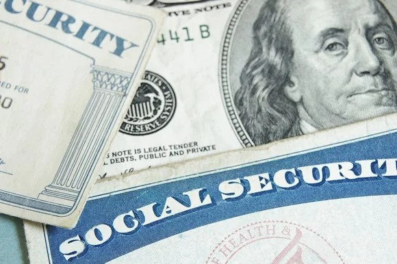 Two Social Security cards lie on top of a hundred-dollar bill.