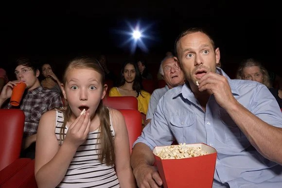 A father and daughter watching a movie.