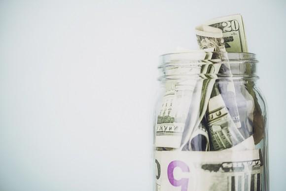Photo of dollar bills in a jar on blue background