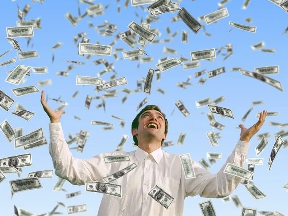 Man smiling with hands outstretched while money falls from the sky