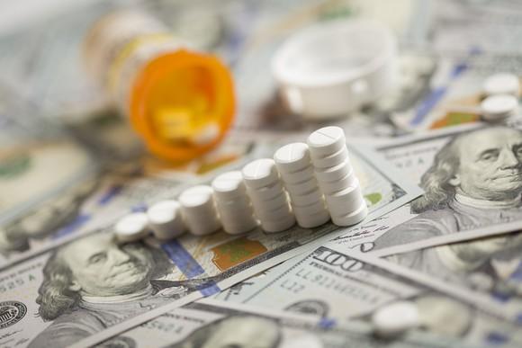 An ascending stack of prescription pills lying on a messy pile of hundred dollar bills.