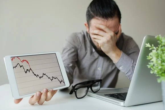 A frustrated investor with his hand covering his face holding up a tablet with a plunging stock chart.