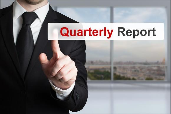 A businessman pressing the quarterly report tab on a digital screen.