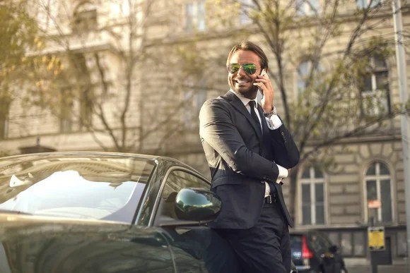Man in a suit talks on a phone in front of a luxury car.