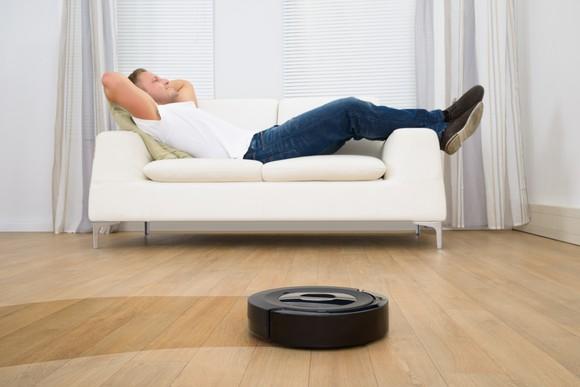 A man reclines as his robotic vacuum sweeps the floor.