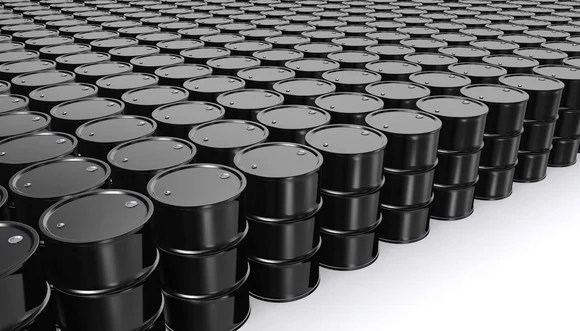 A large number of oil barrels placed in organized rows and columns in a white room.