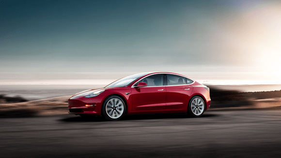 A red Model 3 driving at sunset.