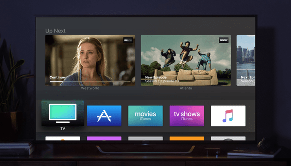 Large TV displaying TVOS interface, with the Apple TV sitting next to it