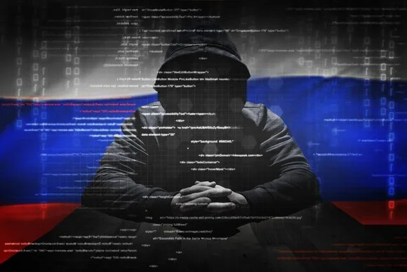 A hacker in front of a Russian flag.