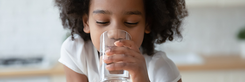 Photo of a young girl drinking a glass of clear water