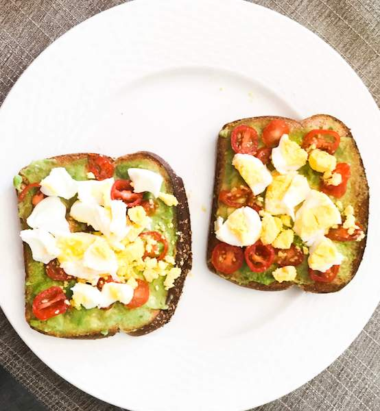 Avocado toasts with cherry tomatoes and boiled eggs