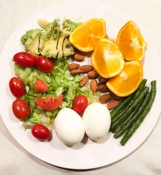 A dinner of salad, oranges, eggs, green peas, almonds, and avocado